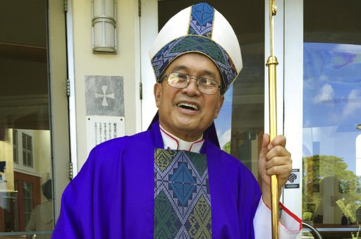 (AP Photo/Grace Garces Bordallo, File). FILE - In this November 2014 file photo, Archbishop Anthony Apuron stands in front of the Dulce Nombre de Maria Cathedral Basilica in Hagatna, Guam. Guam's Catholic church announced Wednesday, Nov. 7, 2018 that i...