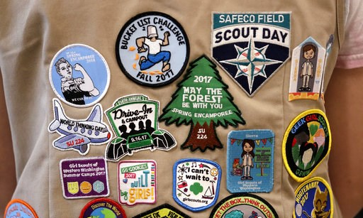 (AP Photo/Elaine Thompson, File). FILE - In this  June 18, 2018, file photo, patches cover the back of a Girl Scout's vest at a demonstration of some of their activities in Seattle. The Girl Scouts of the United States of America filed a trademark infr...