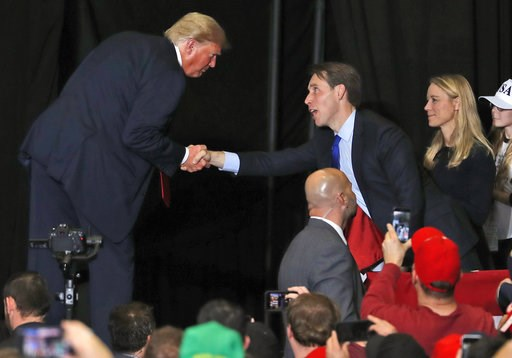 (AP Photo/Jeff Roberson). President Donald Trump shakes hands with Republican Senate candidate Josh Hawley, center, while walking off stage at the end of a campaign rally as Hawley's wife, Erin Hawley, right, watches at the end of a campaign rally Mond...