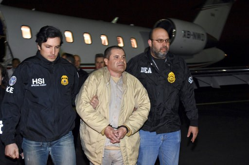 """(U.S. law enforcement via AP, File). FILE - In this Jan. 19, 2017 file photo provided U.S. law enforcement, authorities escort Joaquin """"El Chapo"""" Guzman, center, from a plane to a waiting caravan of SUVs at Long Island MacArthur Airport, in Ronkonkoma,..."""