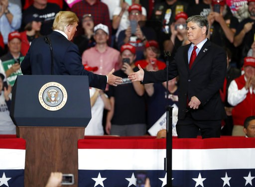 (AP Photo/Jeff Roberson). President Donald Trump shakes hands with Fox News Channel's Sean Hannity, right, during a campaign rally Monday, Nov. 5, 2018, in Cape Girardeau, Mo.