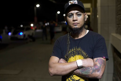 (AP Photo/Moises Castillo). In this Nov. 1, 2018 photo, Honduran migrant Braulio Bustillo, 33, poses for photo as he waits for a bus at the Metropolitan Grand Central bus terminal in San Pedro Sula, Honduras. The tattoo artist agreed to deported after ...