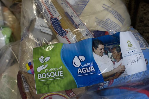 "(AP Photo/Moises Castillo). This Oct. 30, 2018 photo shows ""solidarity bags"" of basic goods that include rice, dried spaghetti and sugar, along with a photo of President Juan Orlando Hernandez and a note saying it comes from his government, at a migran..."