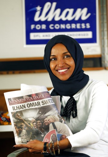 (AP Photo/Jim Mone). Democrat Ilhan Omar holds up a newspaper after she was interviewed by The Associated Press Wednesday, Nov. 7, 2018, in Minneapolis after winning Minnesota's 5th Congressional District race in Tuesday's election. She will be the fir...