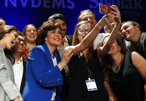 (AP Photo/John Locher). Rep. Jacky Rosen, D-Nev., in blue, poses for a selfie at a Democratic election night party after defeating Sen. Dean Heller, R-Nev., Wednesday, Nov. 7, 2018, in Las Vegas. A female political movement driven by backlash to Presid...