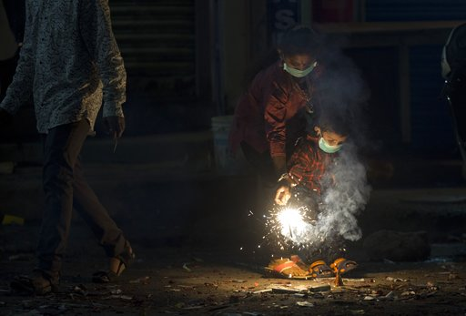 (AP Photo/Mahesh Kumar A.). Indians light fire crackers wearing masks to fight pollution as they celebrate Diwali, the festival of lights in Hyderabad, India, Wednesday, Nov. 7, 2018. India's top court recently ruled that only less polluting firecracke...