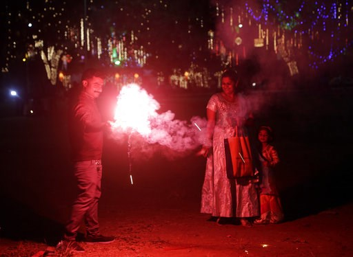 (AP Photo/Rajanish Kakade). Indians light fire crackers as they celebrate Diwali, the festival of lights at a playground in Mumbai, India, Wednesday, Nov. 7, 2018.