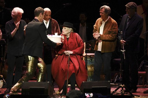 (Photo by Richard Shotwell/Invision/AP). Joni Mitchell is presented with a birthday cake on stage at JONI 75: A Birthday Celebration on Wednesday, Nov. 7, 2018, at the Dorothy Chandler Pavilion in Los Angeles.