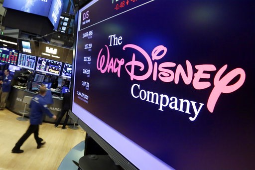 (AP Photo/Richard Drew, File). FILE - In this Aug. 8, 2017, file photo, the Walt Disney Co. logo appears on a screen above the floor of the New York Stock Exchange. The Walt Disney Co. reports earnings Thursday, Nov. 8.