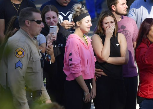 (AP Photo/Mark J. Terrill). People cry as a law enforcement motorcade escorts the body of Ventura County Sheriff's Department Sgt. Ron Helus from the Los Robles Regional Medical Center Thursday, Nov. 8, 2018, in Thousand Oaks, Calif., after a gunman op...