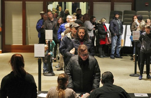 (John R. Ehlke /West Bend Daily News via AP). Julie Skomski checks in with a line of people behind her on Tuesday, Nov. 6, 2018 while voting in the midterm election at the District No. 4 location at CrossWay Church in Germantown, Wis.