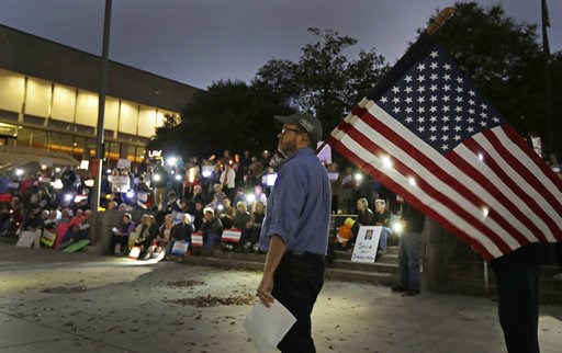 (AP Photo/Chuck Burton). Steve Bird, of Greensboro, N.C., walks past a group of protesters during a rally outside the Guilford County Courthouse against President Trump's Attorney General choice that could jeopardize the special council's work in Green...