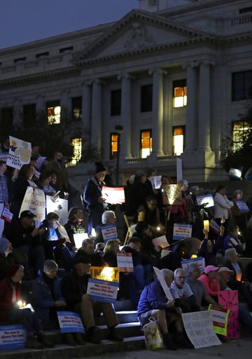 (AP Photo/Chuck Burton). Protesters listen to a speaker during a rally outside the Guilford County Courthouse against President Trump's Attorney General choice that could jeopardize the special council's work in Greensboro, N.C., Thursday, Nov. 8, 2018.