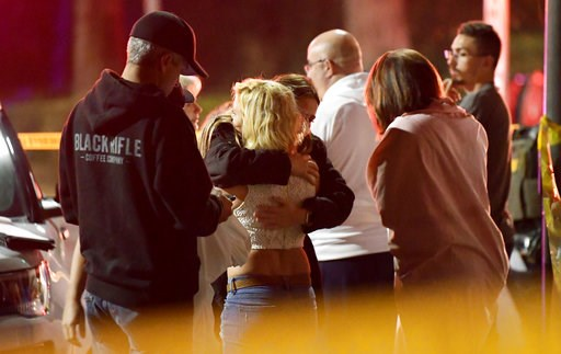 "(AP Photo/Mark J. Terrill). People comfort each other as they stand near the scene Thursday, Nov. 8, 2018, in Thousand Oaks, Calif., where a gunman opened fire Wednesday inside a country dance bar crowded with hundreds of people on ""college night,"" wou..."