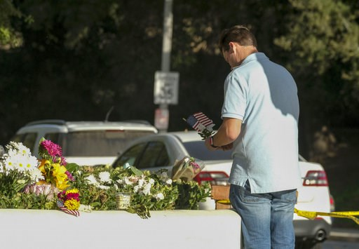 (AP Photo/Ringo H.W. Chiu). Brian White places a U.S. flag with a flower near the scene of a mass shooting Thursday, Nov. 8, 2018, in Thousand Oaks, Calif., after a gunman opened fire Wednesday evening inside a country music bar, killing multiple peopl...
