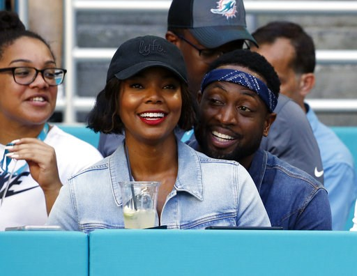 (AP Photo/Joel Auerbach, File). FILE - In this Sunday, Oct. 14, 2018 file photo, Miami Heat player Dwyane Wade and his wife Gabrielle Union-Wade acknowledge the cheers from the crowd during the second half of an NFL football game between the Miami Dolp...