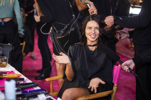 (Photo by Charles Sykes/Invision/AP). Adriana Lima appears backstage during hair and makeup at the 2018 Victoria's Secret Fashion Show at Pier 94 on Thursday, Nov. 8, 2018, in New York.
