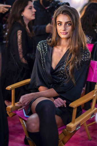 (Photo by Charles Sykes/Invision/AP). Taylor Hill appears backstage during hair and makeup at the 2018 Victoria's Secret Fashion Show at Pier 94 on Thursday, Nov. 8, 2018, in New York.