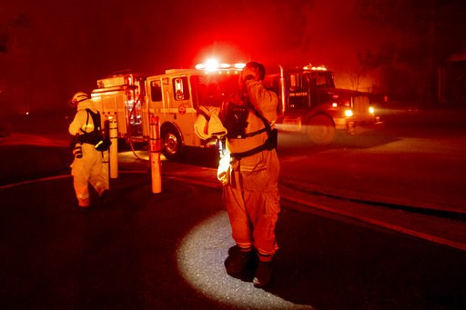(AP Photo/Noah Berger). Firefighter Adrien Mahnke pauses while battling the Camp Fire as it tears through Paradise, Calif., on Thursday, Nov. 8, 2018. Tens of thousands of people fled a fast-moving wildfire Thursday in Northern California, some clutchi...
