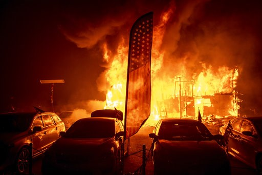 (AP Photo/Noah Berger). Flames consume a car dealership as the Camp Fire tears through Paradise, Calif., on Thursday, Nov. 8, 2018. Tens of thousands of people fled a fast-moving wildfire Thursday in Northern California, some clutching babies and pets ...