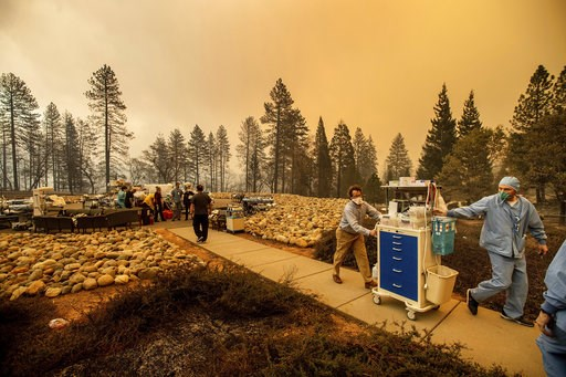 (AP Photo/Noah Berger). Medical workers move equipment from a makeshift emergency room while the Feather River Hospital burns as the Camp Fire rages through Paradise, Calif., on Thursday, Nov. 8, 2018. Tens of thousands of people fled a fast-moving wil...