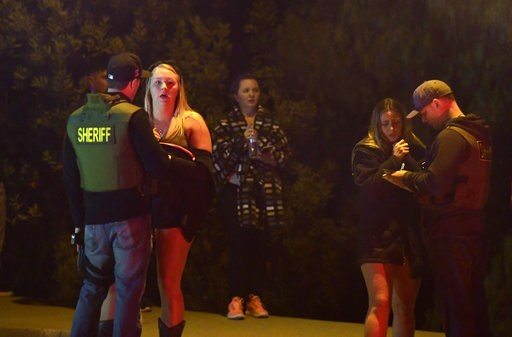 (AP Photo/Mark J. Terrill). Sheriff's deputies speak to potential witnesses as they stand near the scene of a mass shooting Thursday, Nov. 8, 2018, in Thousand Oaks, Calif., where a gunman opened fire Wednesday night inside a country dance bar crowded ...