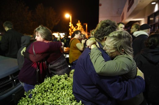 (AP Photo/Jae C. Hong). Eva Mills, right, and Holden Grzywacz, two survivors of the Las Vegas mass shooting, mourn the death of Sean Adler during a vigil at the Rivalry Roasters coffee shop Thursday, Nov. 8, 2018, in Simi Valley, Calif. Adler was kille...