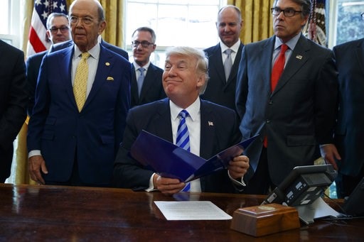 (AP Photo/Evan Vucci, File). FILE - In this March 24, 2017 file photo, President Donald Trump, flanked by Commerce Secretary Wilbur Ross, left, and Energy Secretary Rick Perry, is seen in the Oval Office of the White House in Washington, during the ann...