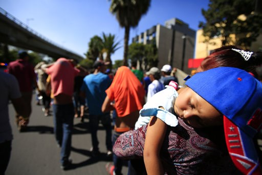 (AP Photo/Rebecca Blackwell). A sleeping Honduran girl is carried as a group of Central American migrants, representing the thousands participating in a caravan trying to reach the U.S. border, undertake an hours-long march to the office of the United ...