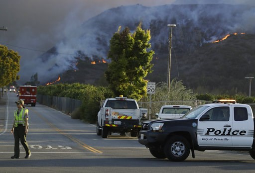 (AP Photo/Marcio Jose Sanchez). A police officer mans a checkpoint in front of an advancing wildfire Thursday, Nov. 8, 2018, near Newbury Park, Calif. The Ventura County Fire Department has ordered evacuation of some communities in the path of the fire...