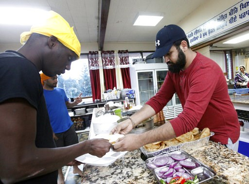 (AP Photo/Amanda Loman). In this Wednesday, Oct. 3, 2018, photo, Karandeep Singh, right, serves a bowl of curry to Abdoulaye Camara at the Dasmesh Darbar Sikh temple in Salem, Ore. Both are immigrants who were recently freed from the federal prison in ...