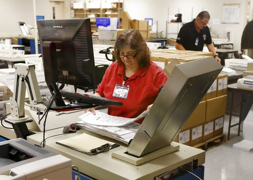 (AP Photo/Ross D. Franklin). Workers prepare ballots for counting machines at the Maricopa County Recorder's Office Thursday, Nov. 8, 2018, in Phoenix.
