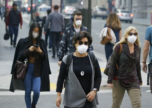 (AP Photo/Eric Risberg). People wear masks while walking through the Financial District in the smoke-filled air Friday, Nov. 9, 2018, in San Francisco. Authorities have issued an unhealthy air quality alert for parts of the San Francisco Bay Area as sm...
