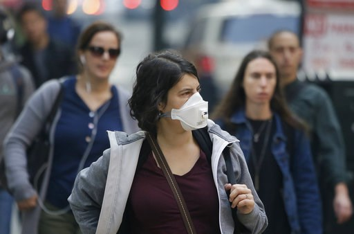 (AP Photo/Eric Risberg). A woman wears a mask while walking through the Financial District in the smoke-filled air Friday, Nov. 9, 2018, in San Francisco. Authorities have issued an unhealthy air quality alert for parts of the San Francisco Bay Area as...