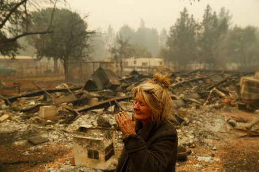 "(AP Photo/John Locher). Cathy Fallon reacts as she stands near the charred remains of her home, Friday, Nov. 9, 2018, in Paradise, Calif. ""I'll be darned if I'm going to let those horses burn in the fire,"" said Fallon, who stayed on her property to pro..."