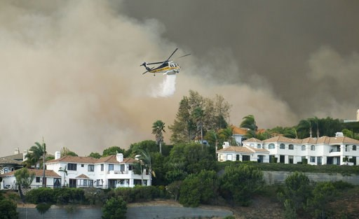 (AP Photo/Ringo H.W. Chiu). A helicopter drops water on a brush fire behind homes during the Woolsey Fire in Malibu, Calif., Friday, Nov. 9, 2018. A fast-moving wildfire in Southern California has scorched a historic movie site recently used by the HBO...