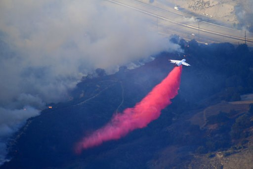 (AP Photo/Mark J. Terrill). An air tanker drops flame retardant to protect homes as fires burn Friday, Nov. 9, 2018, as seen from a helicopter over the Calabasas section of Los Angeles. Flames driven by powerful winds torched dozens of hillside homes i...