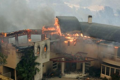 (AP Photo/Ringo H.W. Chiu). The Woolsey Fire burns a home near Malibu Lake in Malibu, Calif., Friday, Nov. 9, 2018.