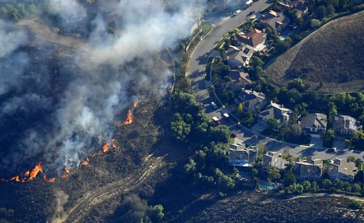 (AP Photo/Mark J. Terrill). Fires burn toward homes Friday, Nov. 9, 2018, as seen from a helicopter over the Calabasas section of Los Angeles. Flames driven by powerful winds torched dozens of hillside homes in Southern California, burning parts of ton...
