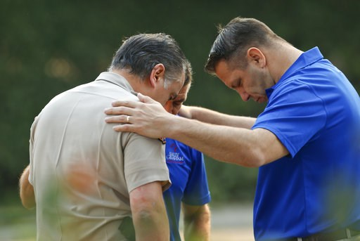 (AP Photo/Damian Dovarganes). Ventura County Sheriff's Office Capt. Garo Kuredjian, left, embraces chaplains with the Billy Graham Rapid Response Team (RRT) as they pray near the site of Wednesday's mass shooting in Thousand Oaks, Calif., Friday Nov. 9...