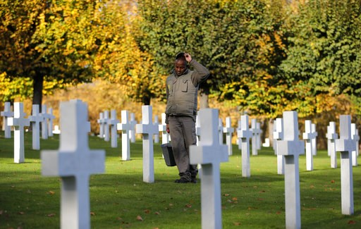 (AP Photo/Vadim Ghirda). A cemetery employee walks between graves of American serviceman killed during WWI ahead of celebrations of the WWI centenary at the American Cemetery in Suresnes, on the outskirts of Paris, France, Friday, Nov. 9, 2018. World W...