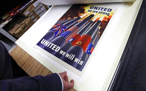 (AP Photo/Charles Krupa). Brian Sylvester, director of the Rochester Public Library, examines original war posters at the library's archive in Rochester, N.H., Thursday, Nov. 8, 2018. A trove of propaganda posters from World War I and II were found rec...