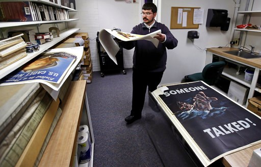(AP Photo/Charles Krupa). Brian Sylvester, director of the Rochester Public Library, carries an original war poster at the library's archive in Rochester, N.H., Thursday, Nov. 8, 2018. A trove of propaganda posters from World War I and II were found re...