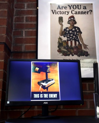 (AP Photo/Charles Krupa). A National War Garden Commission poster copy hangs in a hallway as a display loop shows historic posters on monitor at the Rochester Public Library in Rochester, N.H., Thursday, Nov. 8, 2018. A trove of propaganda posters from...