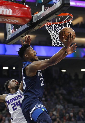 (AP Photo/Steve Yeater). Minnesota Timberwolves guard Jimmy Butler (23) gets around Sacramento Kings guard Buddy Hield (24) for a basket during the first half of an NBA basketball game in Sacramento, Calif., Friday, Nov. 9, 2018.