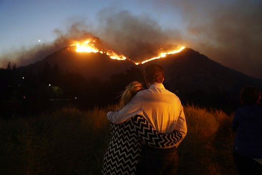 (AP Photo/Marcio Jose Sanchez). Roger Bloxberg, right, and his wife Anne hug as they watch a wildfire on a hill top near their home Friday, Nov. 9, 2018, in West Hills, Calif.