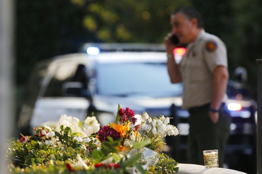 (AP Photo/Damian Dovarganes). A bouquet of flowers, left by mourners, lays near the site of Wednesday's mass shooting, in Thousand Oaks, Calif., Friday, Nov. 9, 2018. Investigators continue to work to figure out why an ex-Marine opened fire Wednesday e...