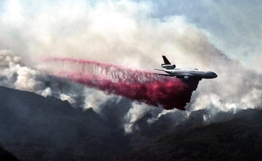 (AP Photo/Richard Vogel). A firefighting DC-10 makes a fire retardant drop over a wildfire in the mountains near Malibu Canyon Road in Malibu, Calif. on Sunday, Nov. 11, 2018. Strong Santa Ana winds have returned to Southern California, fanning a huge ...