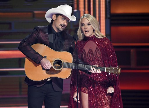 (Photo by Chris Pizzello/Invision/AP, File). FILE - This Nov. 8, 2017 file photo shows hosts Brad Paisley, left, and Carrie Underwood during the opening of the 51st annual CMA Awards in Nashville, Tenn. Underwood will be working triple-duty at the 2018...