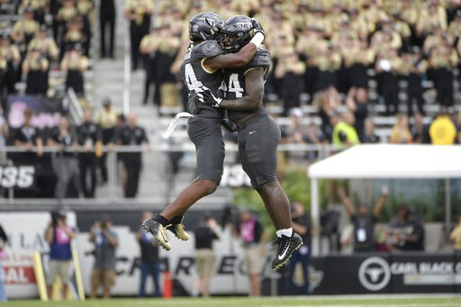 (AP Photo/Phelan M. Ebenhack). FILE - In this Nov. 10, 2018, file photo, Central Florida linebacker Gabriel Luyanda, left, and linebacker Nate Evans celebrate after the team recovered a fumble during the first half of an NCAA college football game agai...